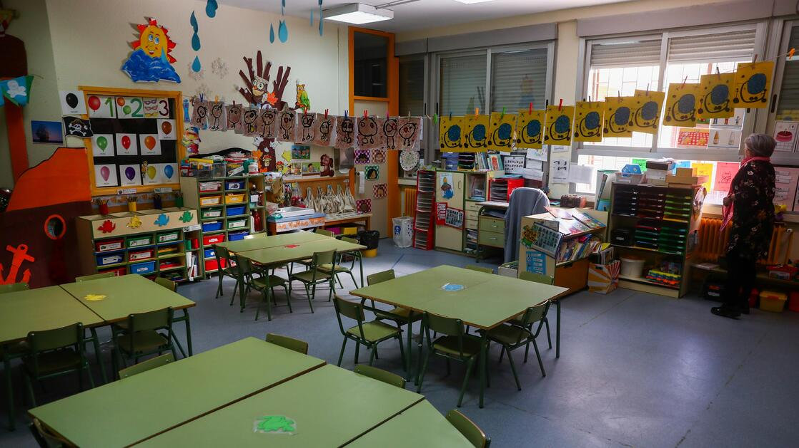 A teacher raises a shutter inside an empty classroom in a closed school in Madrid.